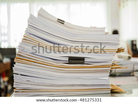 Large stack of business report paper files with black clips
