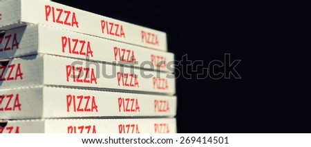 Large stack of pizza boxes. Isolated over black. - stock photo