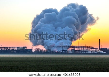 Large Stack of Smoke from metallurgical Power Plant at Sunrise orange Sky Background and Green freshly tilled agriculture Field on Foreground - stock photo