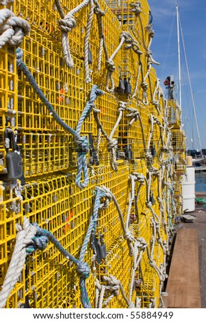 Large stack of yellow commercial lobster traps with a boats mast in the background - stock photo