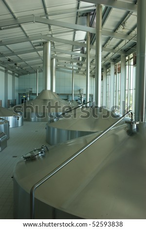 Large stainless steel vats in a large commercial distillery - stock photo