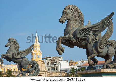 Large statues of Pegasus, the flying horse, on the road leading to the historic Clock Tower (Torre del Reloj) and main gateway into the historic walled city of Cateragena de Indias in Colombia - stock photo