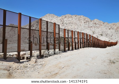 Large steel fence protecting the border between Mexico and the United States of America at the Tinajas Altas Mountains in Arizona (Sonoran Desert). Common place for illegals & drug smugglers to cross. - stock photo