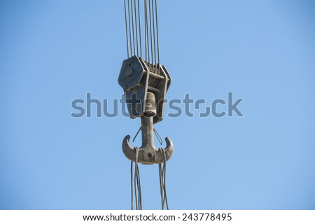 Large steel hook on cables of heavy industrial crane machinery against blue sky background - stock photo