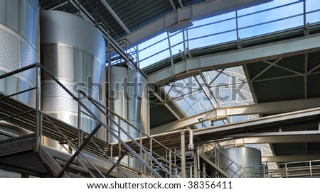 Large steel vats are glittering in the middle of shining pipes and stairs of modern winery. Bright sunlight are streaming through big windows on roof.
