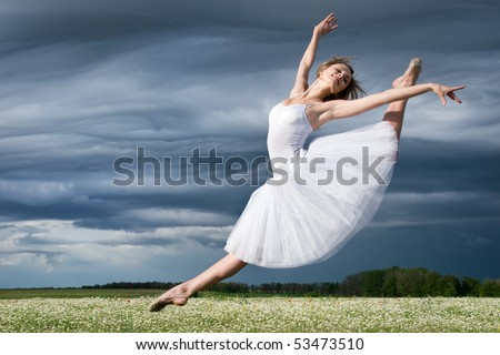 large step of beautiful ballet dancer against cloudy sky - stock photo