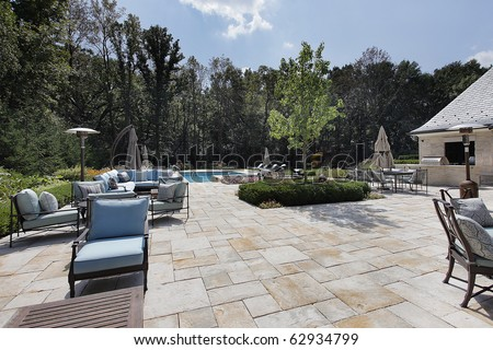 Large stone patio of luxury home with swimming pool - stock photo