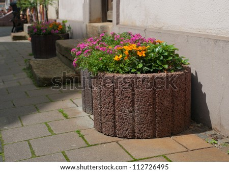 large stone planters with blooming flowers on a sidewalk - stock photo