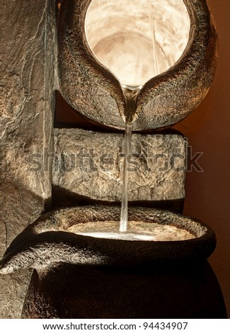 Large stone pot vessels are pouring water from one container to the next in a darkened place with light coming from inside, for a dramatically lit still life. - stock photo