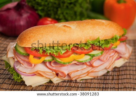 Large sub with fresh veggies, cheese, turkey and ham - stock photo