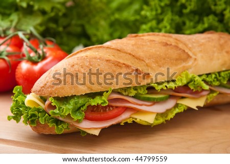 Large submarine sandwich with ham, swiss cheese, lettuce and tomatos on a wooden cutting board