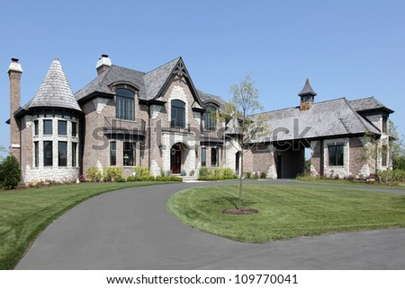 Large suburban brick and stone home with circular driveway - stock photo