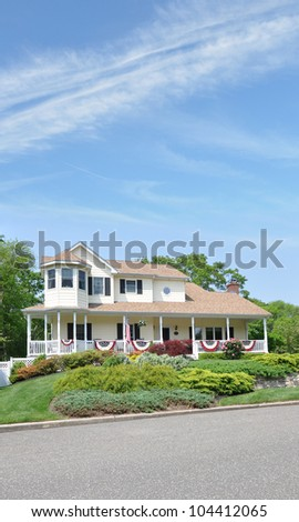 Large Suburban Home Decorated with American Flags for Memorial Day and July 4 Independence Holiday Sunny Blue Sky Day