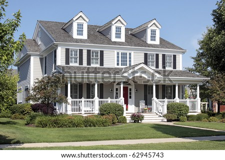 Large suburban home with front porch and arched entry - stock photo