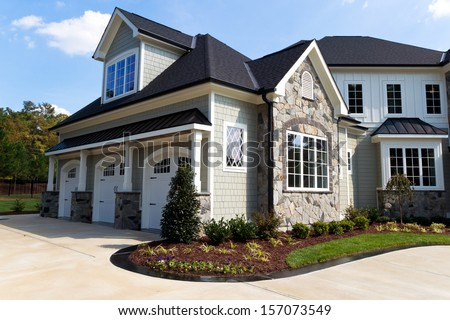 Large suburban house exterior with tree car garage - stock photo