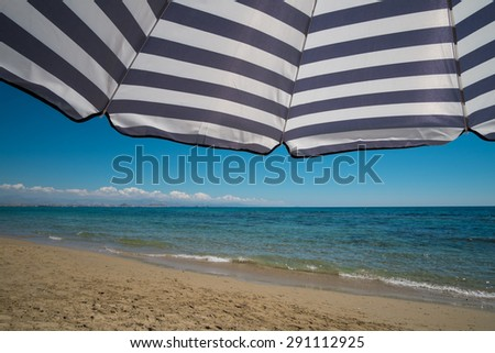 Large sunshade against the background of a sunny beach - stock photo