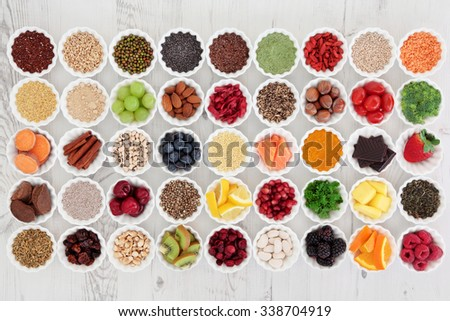 Large super food selection in porcelain crinkle bowls over distressed wooden background. High in vitamins and antioxidants. - stock photo