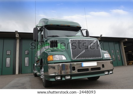 large super-truck, lorry standing in front of gates, trademarks removed - stock photo