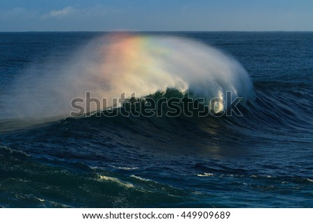 Large surf wave with rainbow colour in spray - stock photo