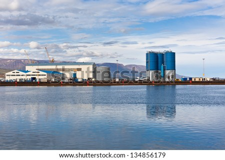 Large tanks and wirehouses at sea commercial dock in North Iceland. Horizontal shot