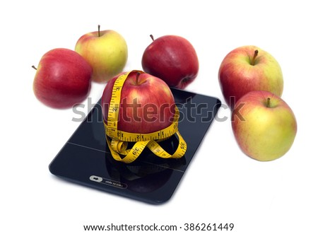 Large  tasty red and yellow ripe apples on kitchen scales and measuring tape isolated on white background. Top side view closeup - stock photo