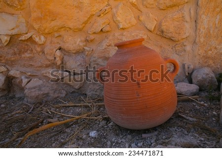 Large terracotta water urn rests in front of a stone wall  - stock photo