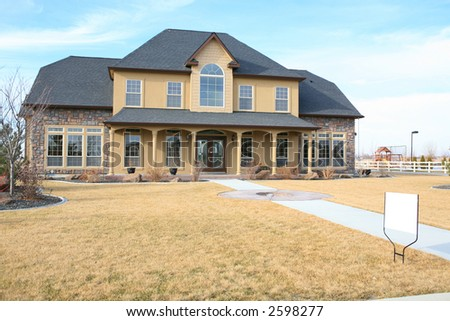 Large three story house with blank real estate sign in yard - stock photo