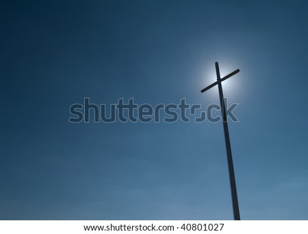 Large towering Cross silhouette with afternoon Sun glow and copy space - stock photo