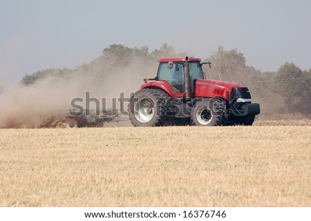 Large tractor pulling plow, throwing dust up in the air. Ukraine