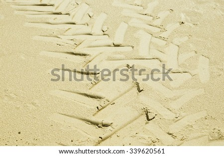 large tractor tyre tracks on beach sand in bright sunlight - stock photo