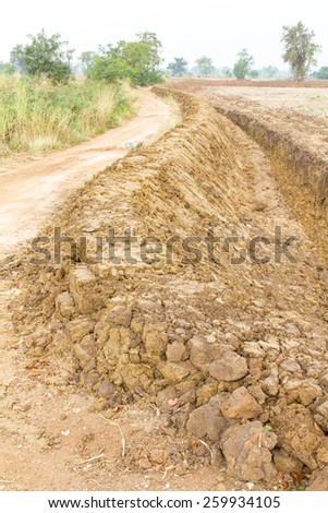 Large trench dug in the ground rice Thailand to store water for farming. - stock photo