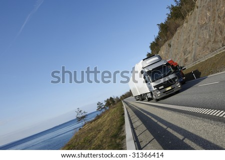 large truck driving on highway with scenic surrounding of sea and mountain-pass - stock photo