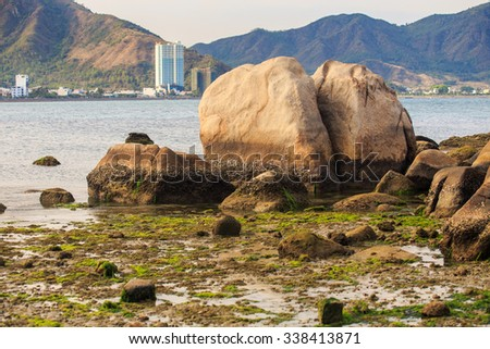 large twins stones in shallow sea water against distant resort city at foot of hill of tropical island - stock photo