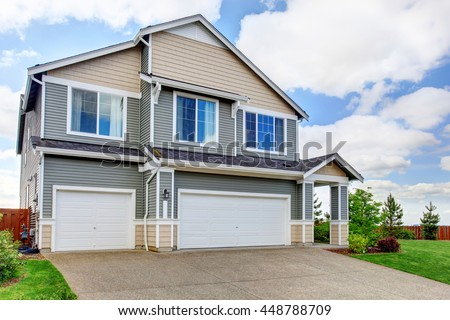 Large two story house with siding, two garage spaces and concrete driveway. House exterior.