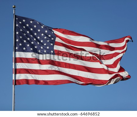"""Large U.S. Flag """"Old Glory"""" blowing in a strong wind on a cloudless day - stock photo"""