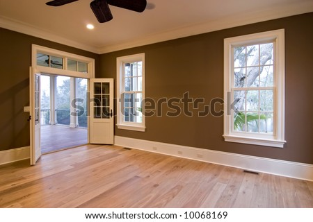 large unfurnished bedroom or diningroom with open doors to porch - stock photo