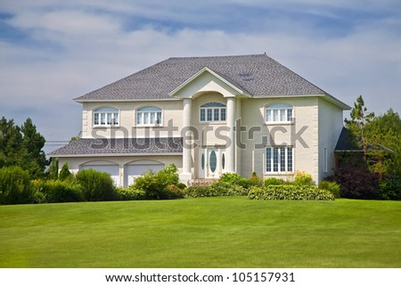 Large upscale family home with a beautiful lawn. - stock photo