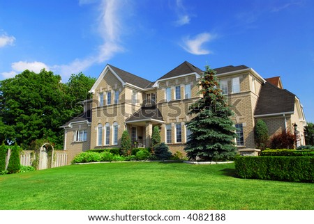Large upscale residential home with bright green lawn and blue sky - stock photo