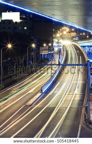 Large urban highway viaduct light trails night scene - stock photo