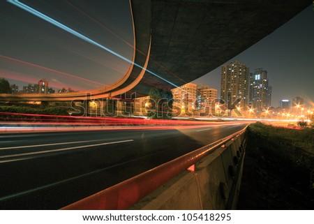 Large urban ring highway viaduct long exposure photo light trails night scene - stock photo