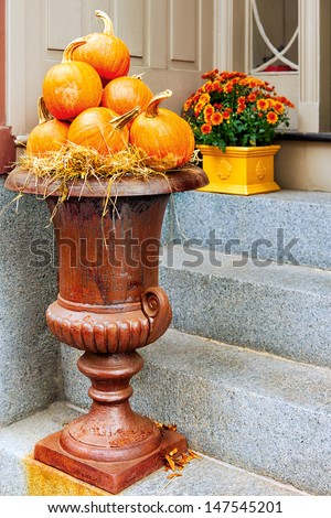 Large urn filled with pumpkins outside on the steps leading to the front door. Seasonal display for Halloween, Thanksgiving, fall and autumn. - stock photo