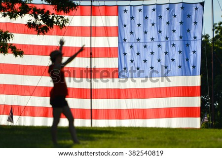 Large US Flag hanging on a meadow and silhouette of young woman - Washington DC USA