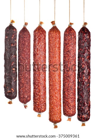 large variety of vertically arranged salami sausages isolated on white background