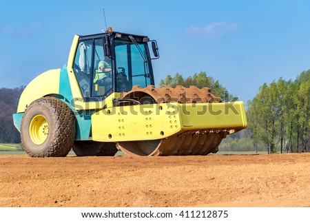 Large view on the compactor working on the new road construction site - stock photo