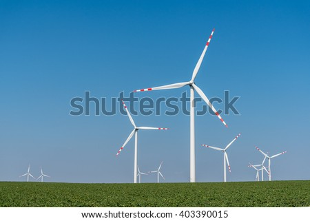 Large view on the windmills on the large green field