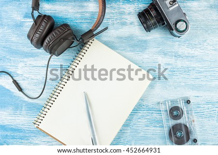 Large Vintage Leather headphones to play music lie next to a blank notebook with a ballpoint pen, photo camera and audio tape on blue wooden background. Mock up. Top view. Flat lay. - stock photo