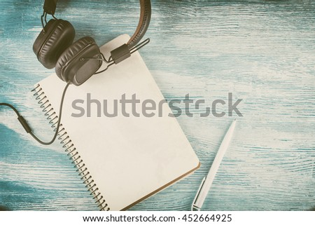 Large Vintage Leather headphones to play music lie next to a blank notebook with a ballpoint pen on blue wooden background. Mock up. Top view. Flat lay. Toned. Old photo styled - stock photo