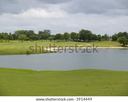 Large water hindrance at a golf course. Fairway, trees and heavy, black clouds in the background. - stock photo