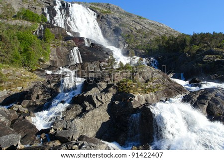 large waterfall in the summer woods, norway