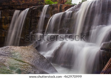 Large waterfall photographed closeup. Use a slow shutter. Waterfall slow and stagnant beautiful and gorgeous. Focus at Waterfalls. A highlight trees and sky background blur.